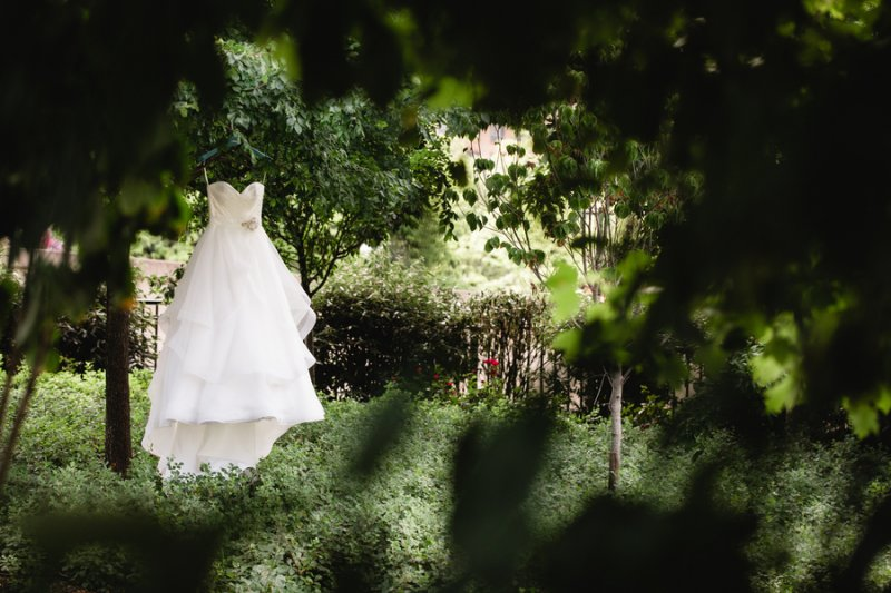 wedding dress hanging in garden