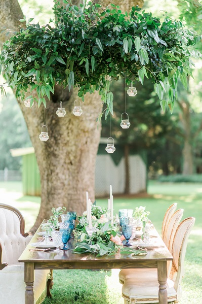 greenery hanging over tablescape with mini lanterns
