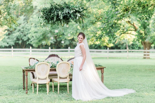 bride standing next to tablescape