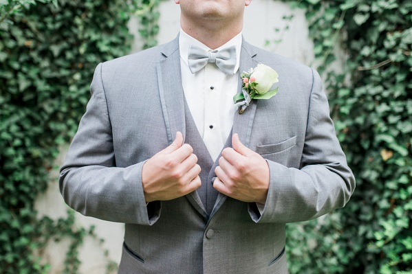 groom adjusting grey jacket