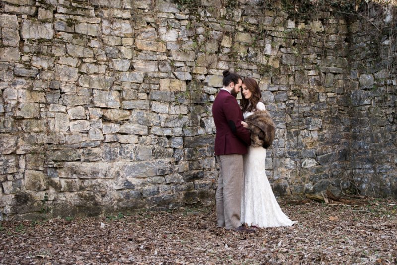 bride in a faux fur shawl and groom in a burgundy jacket
