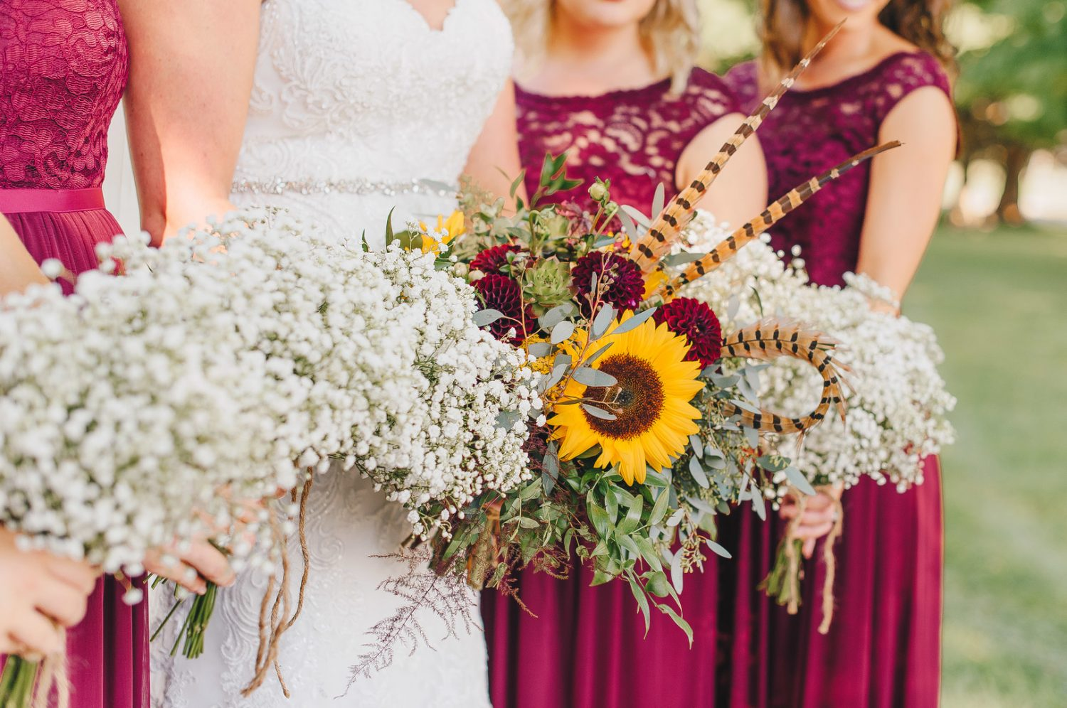 burgundy bridesmaid dresses with sunflower and baby's breath arrangements