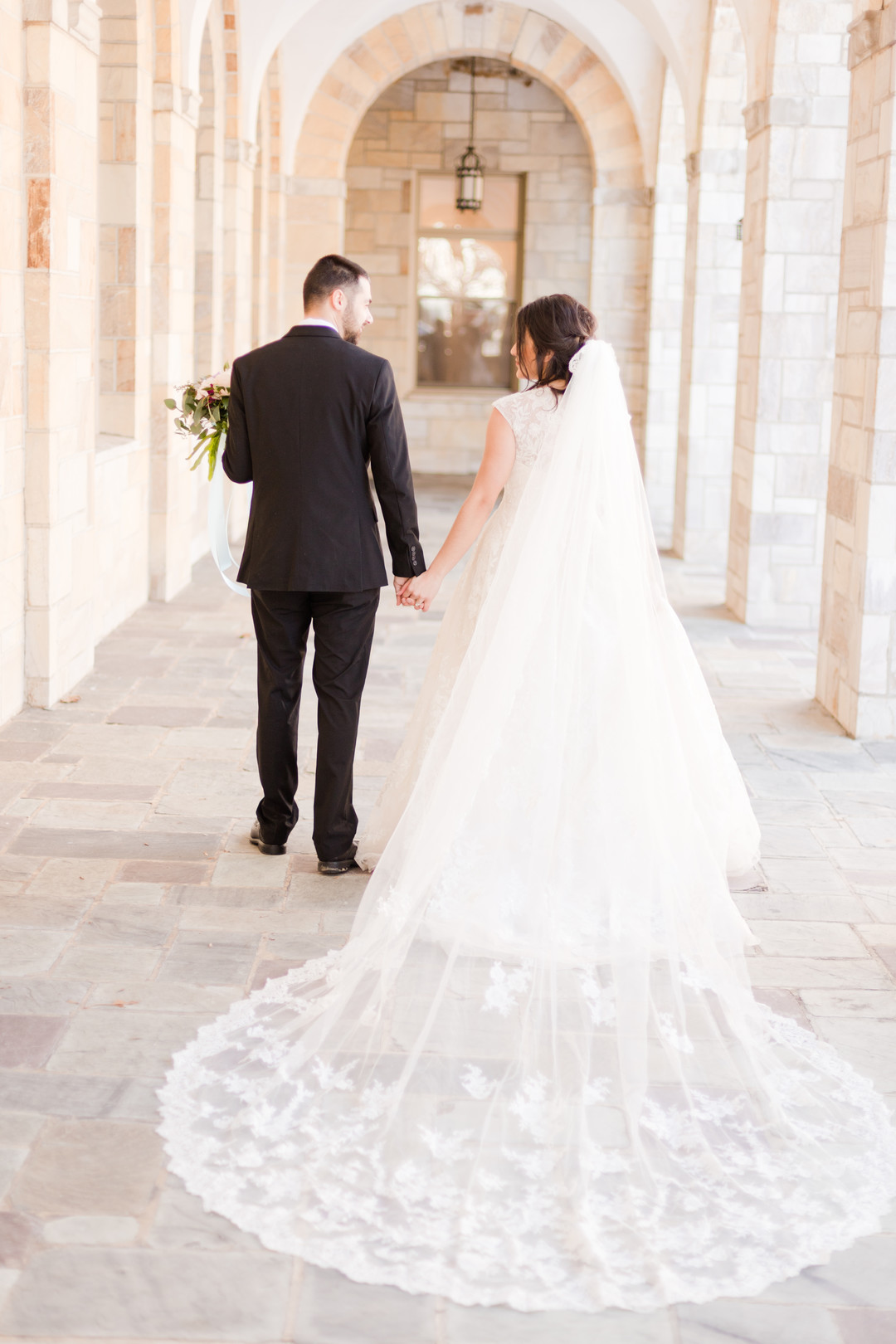 bride and groom at shrine of st Anthony with long veil