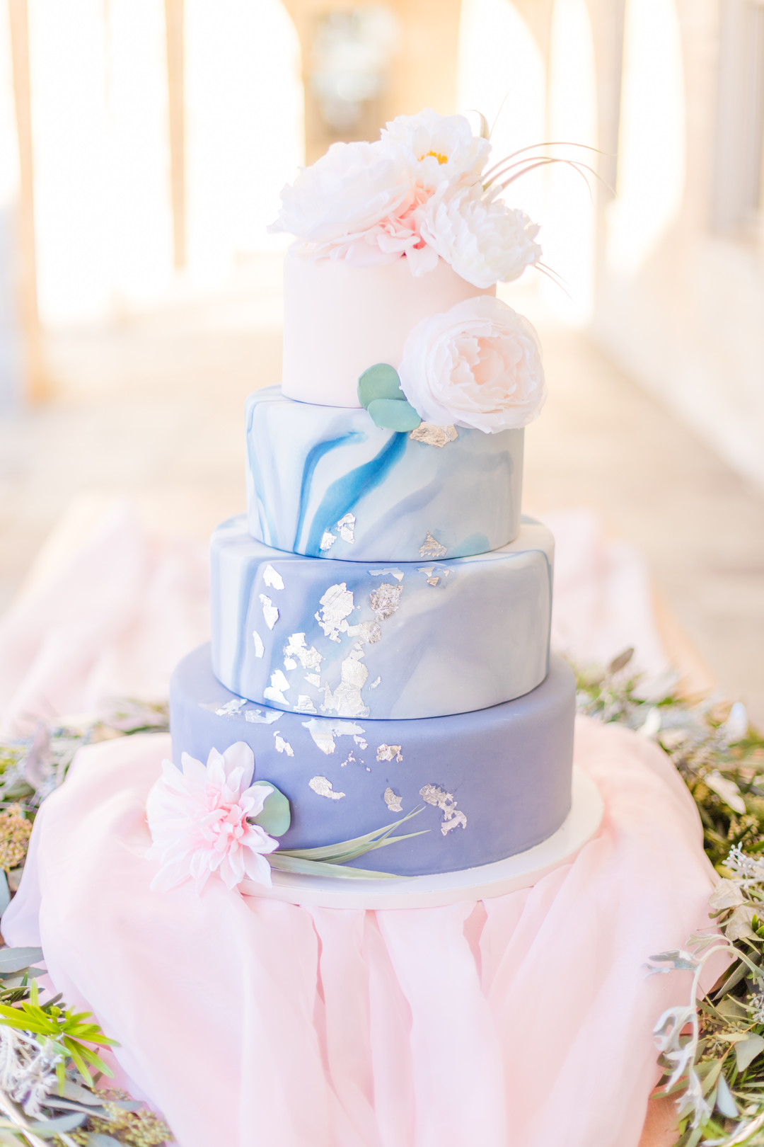 light blue purple and pink wedding cake with gold foil and marble