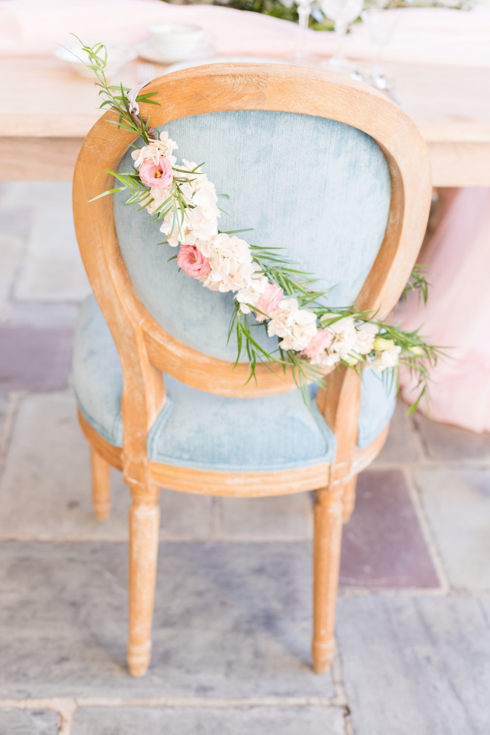 light blue chair with floral and greenery sash