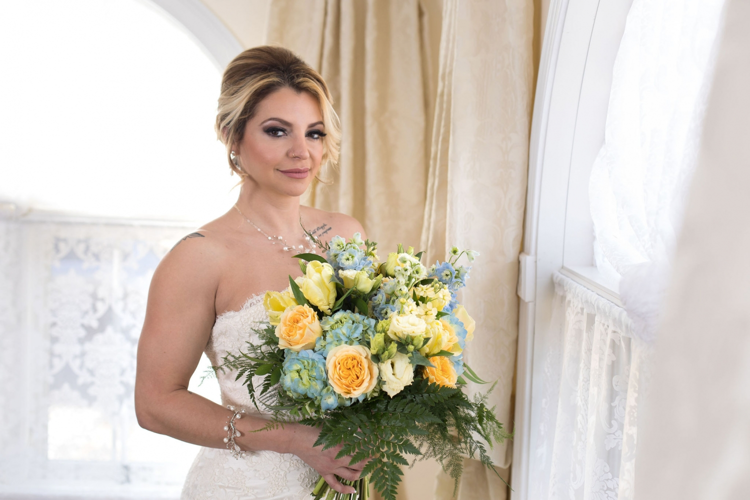bride holding a yellow bouquet