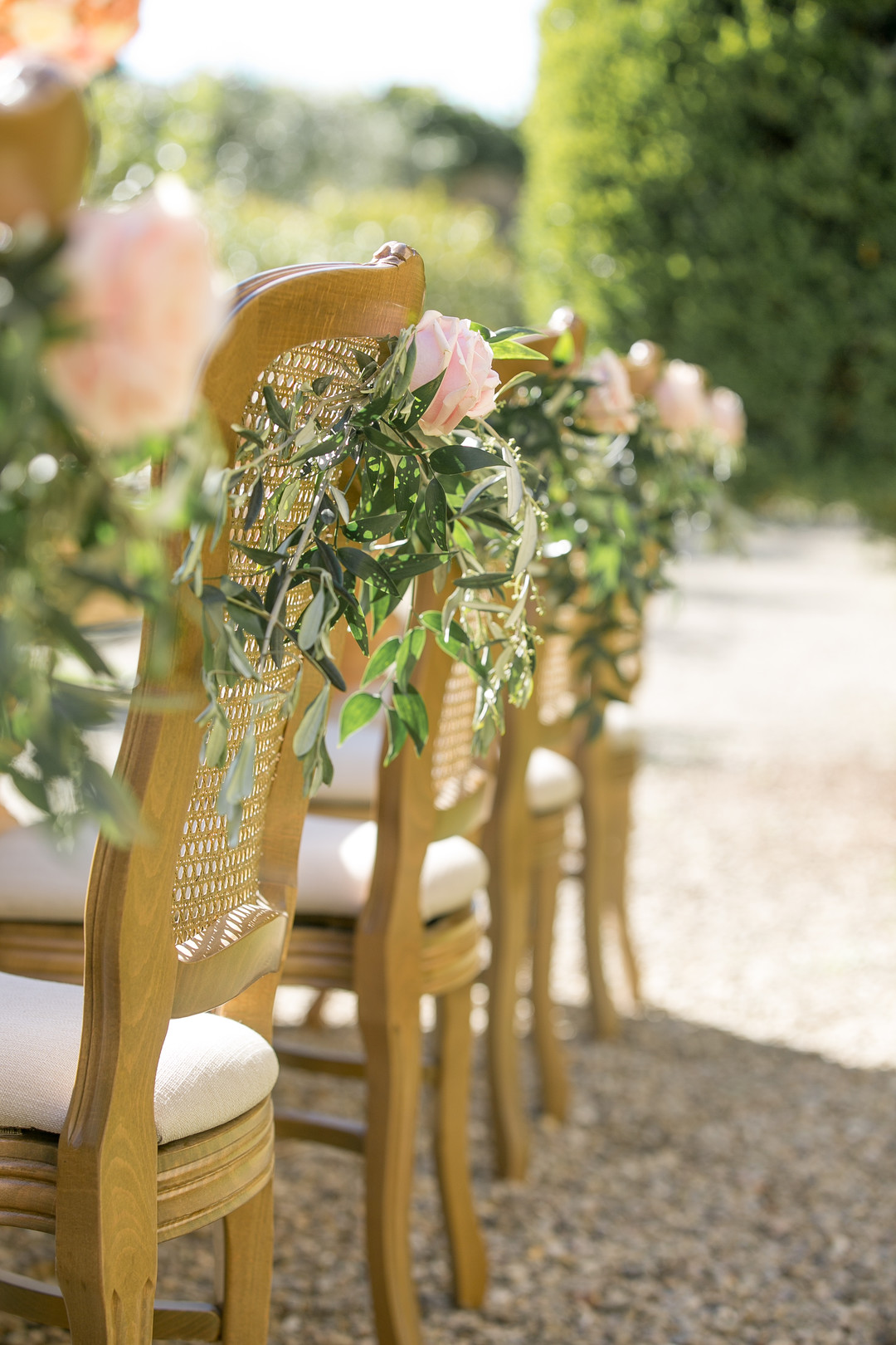 wedding chairs decorated with pink roses