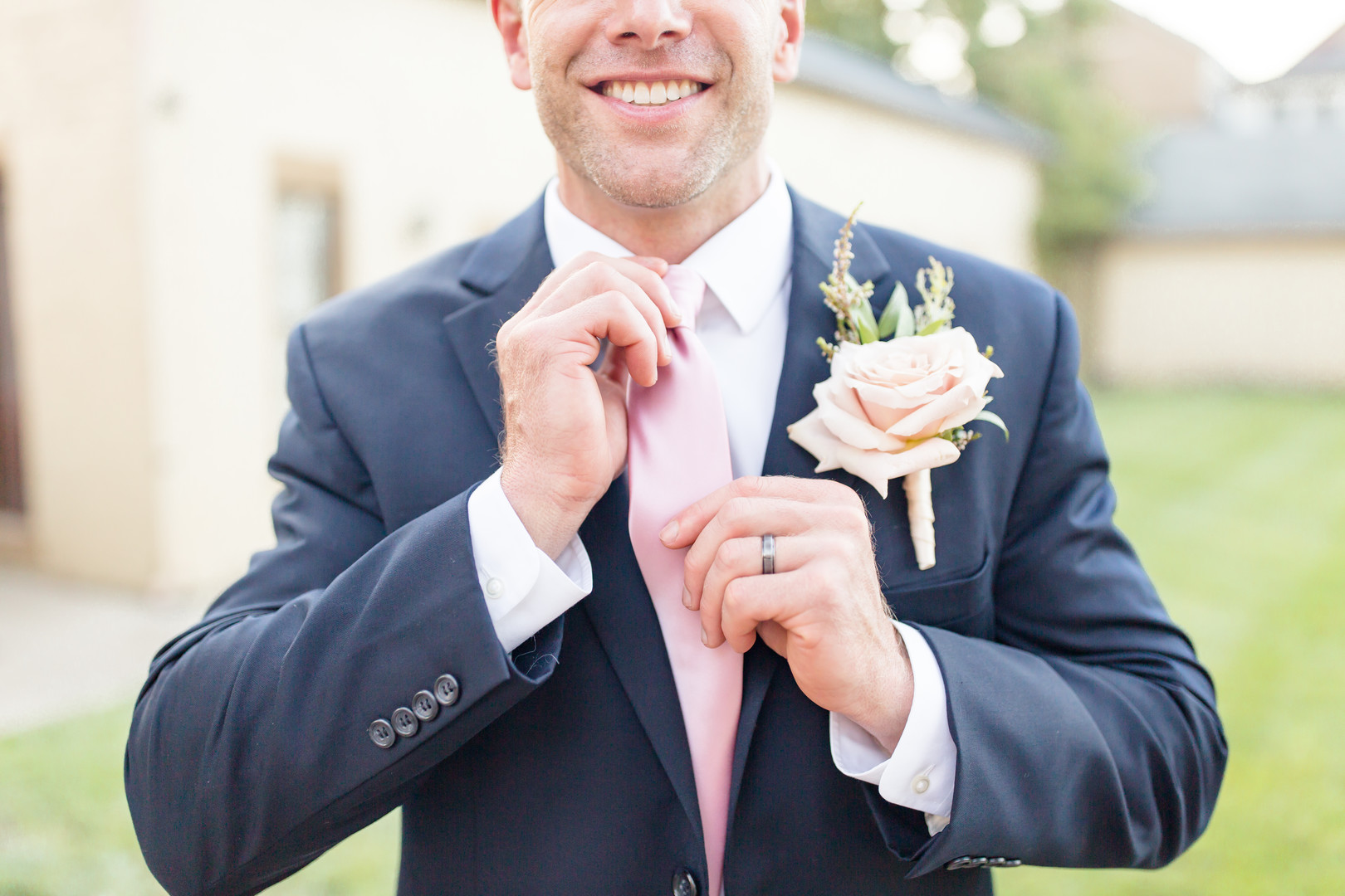 groom with large rose boutonniere