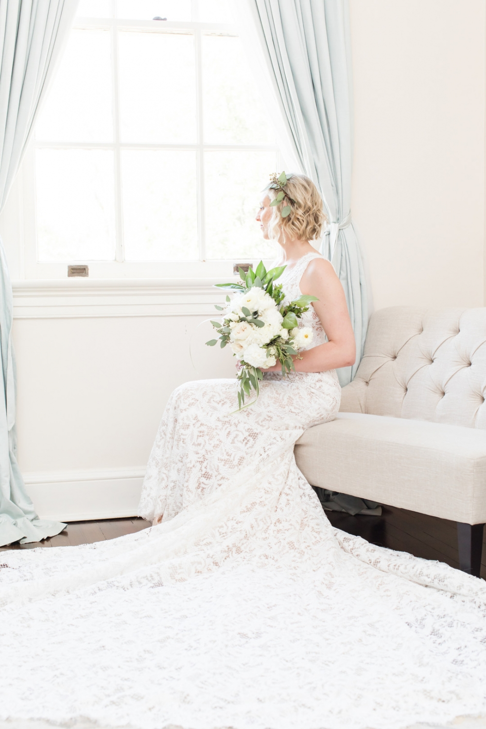Bride sitting by window on a white couch