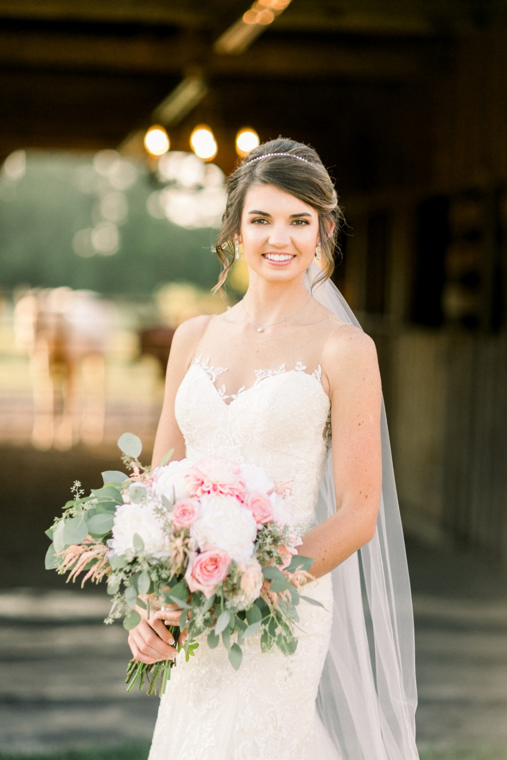 bride holding a bouquet in a horse stable