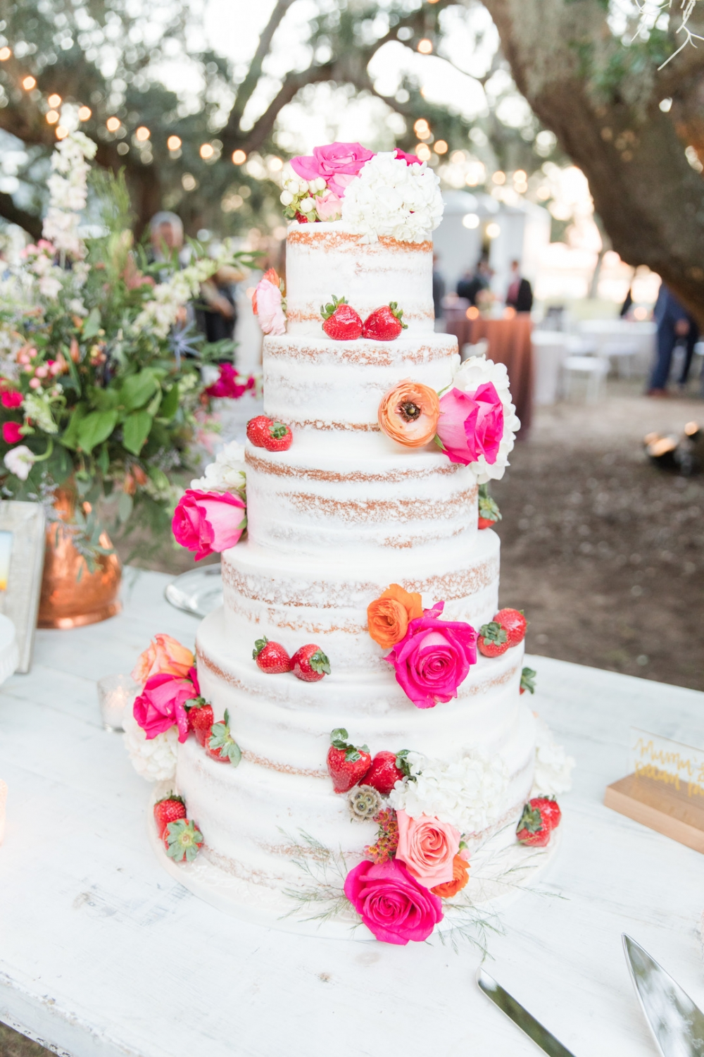 6 tier cake with pink flowers and strawberries