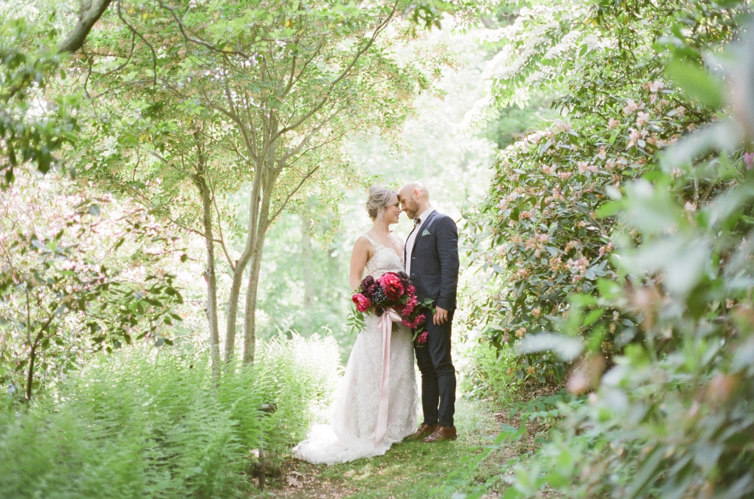 Bride and Groom photo in the garden with pink bouquet