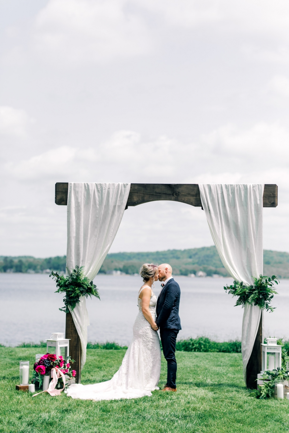 ceremony backdrop with white fabric and greenery