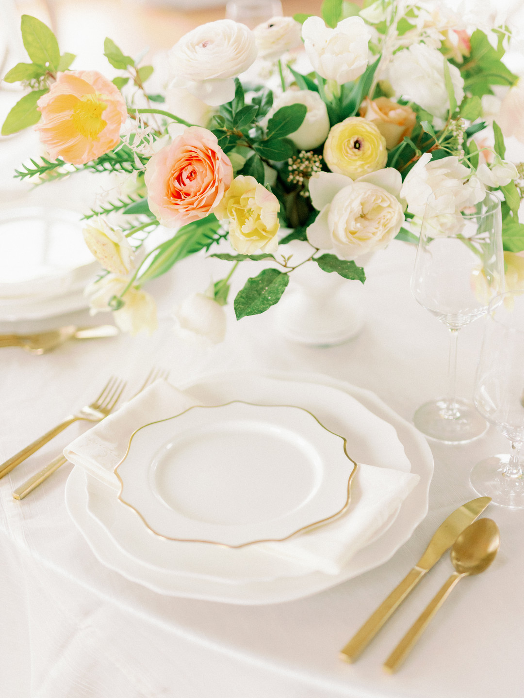 soft ivory twist linen with a magnolia charger and plate accented with a trieste gold salad plate and flatware.