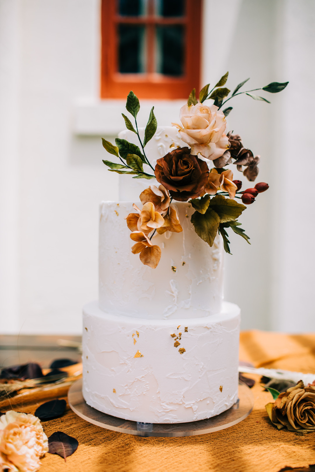 two-tiered fall wedding cake with some added florals