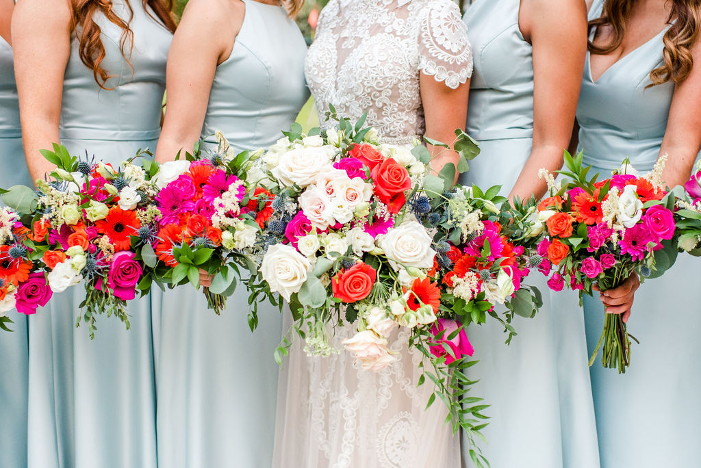 pink and orange flowers with blue bridesmaid dresses