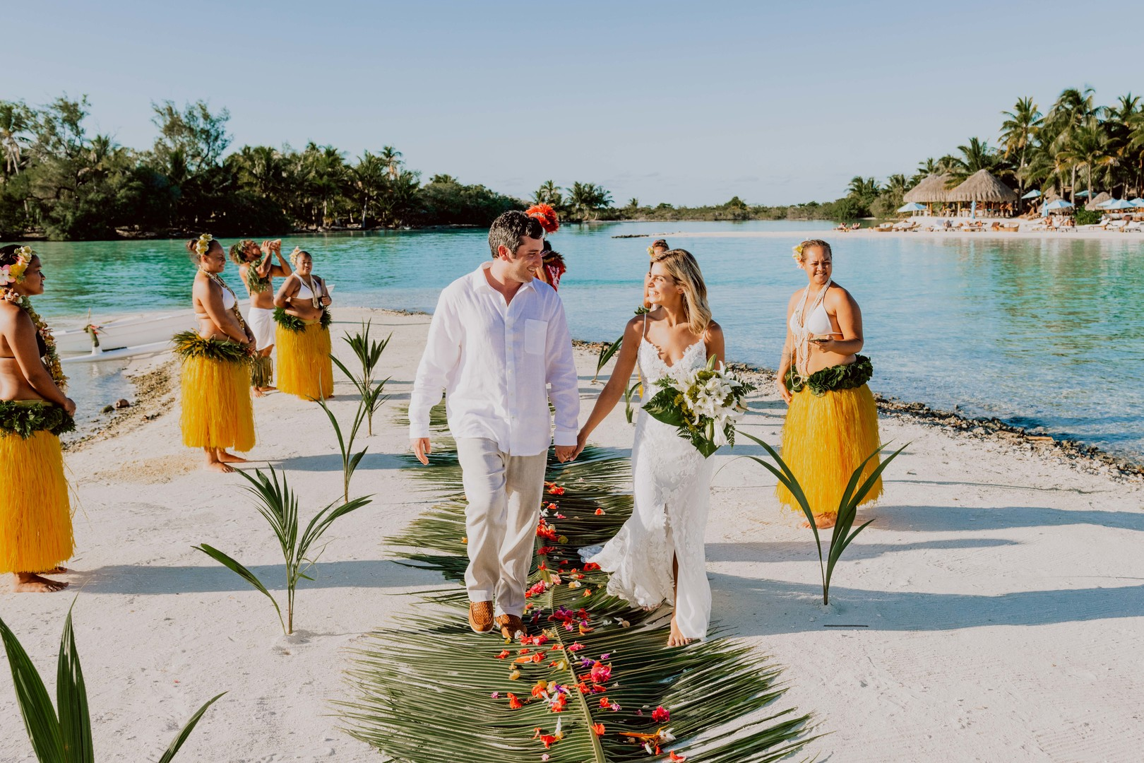 Bora Bora wedding ceremony with couple walking on palm leaves and rose petals