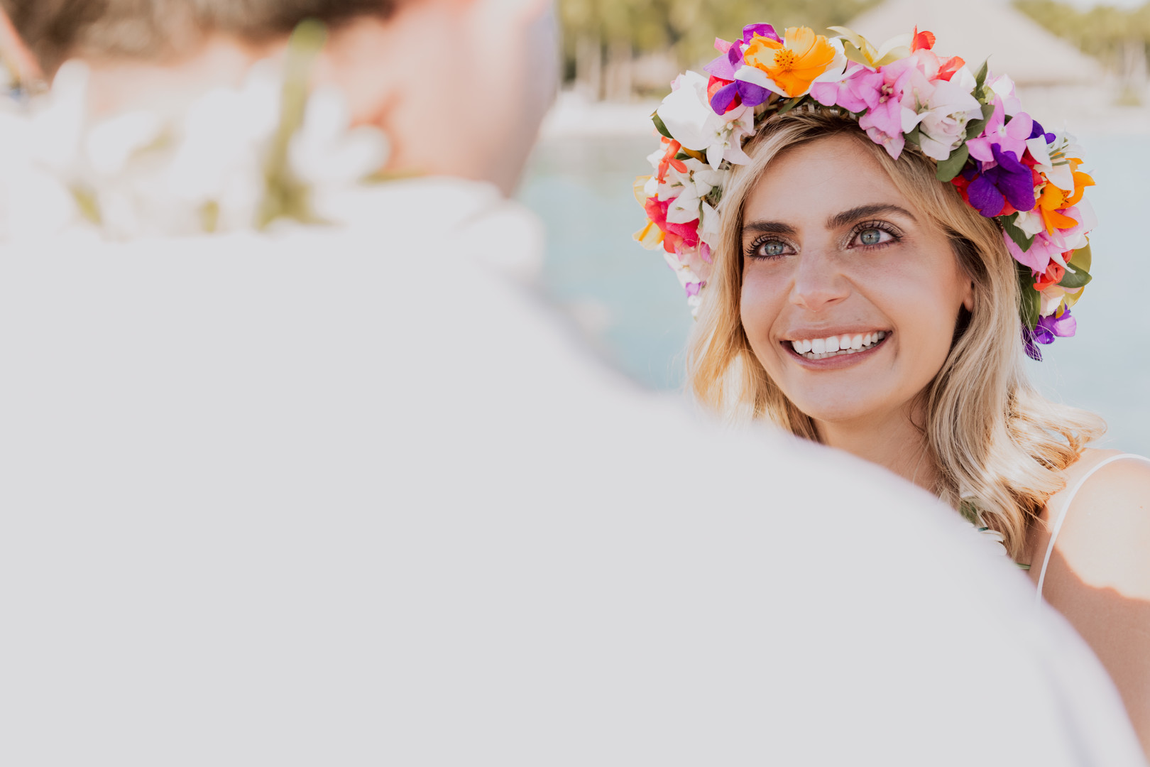 bride looks at groom during wedding in bora bora with a colorful floral garland