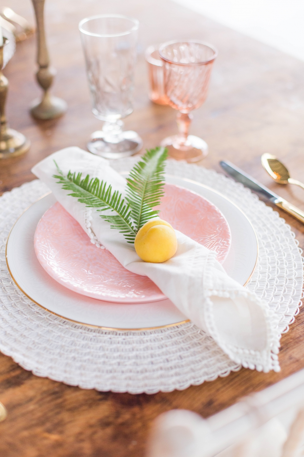 pink and white place setting with a peach