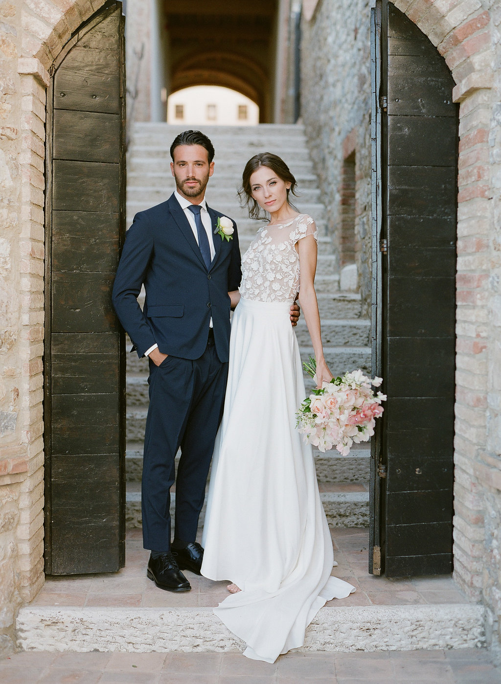 bride and groom posing in a Tuscan winery hallway