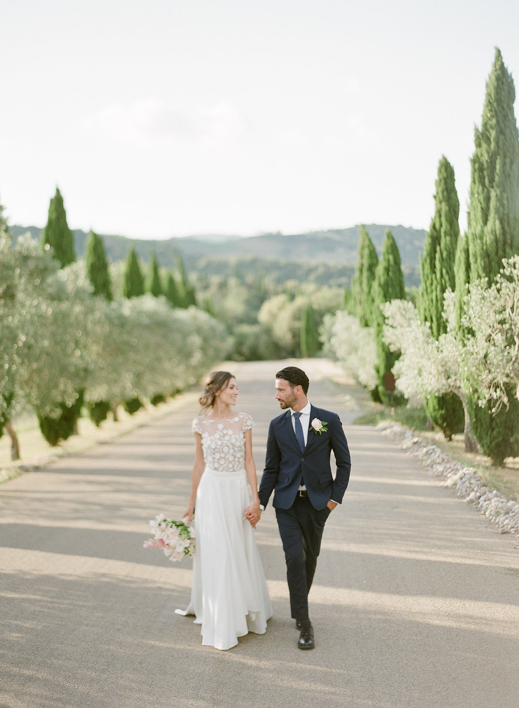bride and groom walking along a Tuscan road