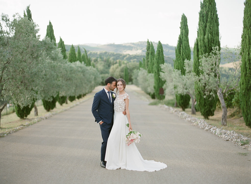 bride and groom walking along a Tuscan roadway leading up to winery