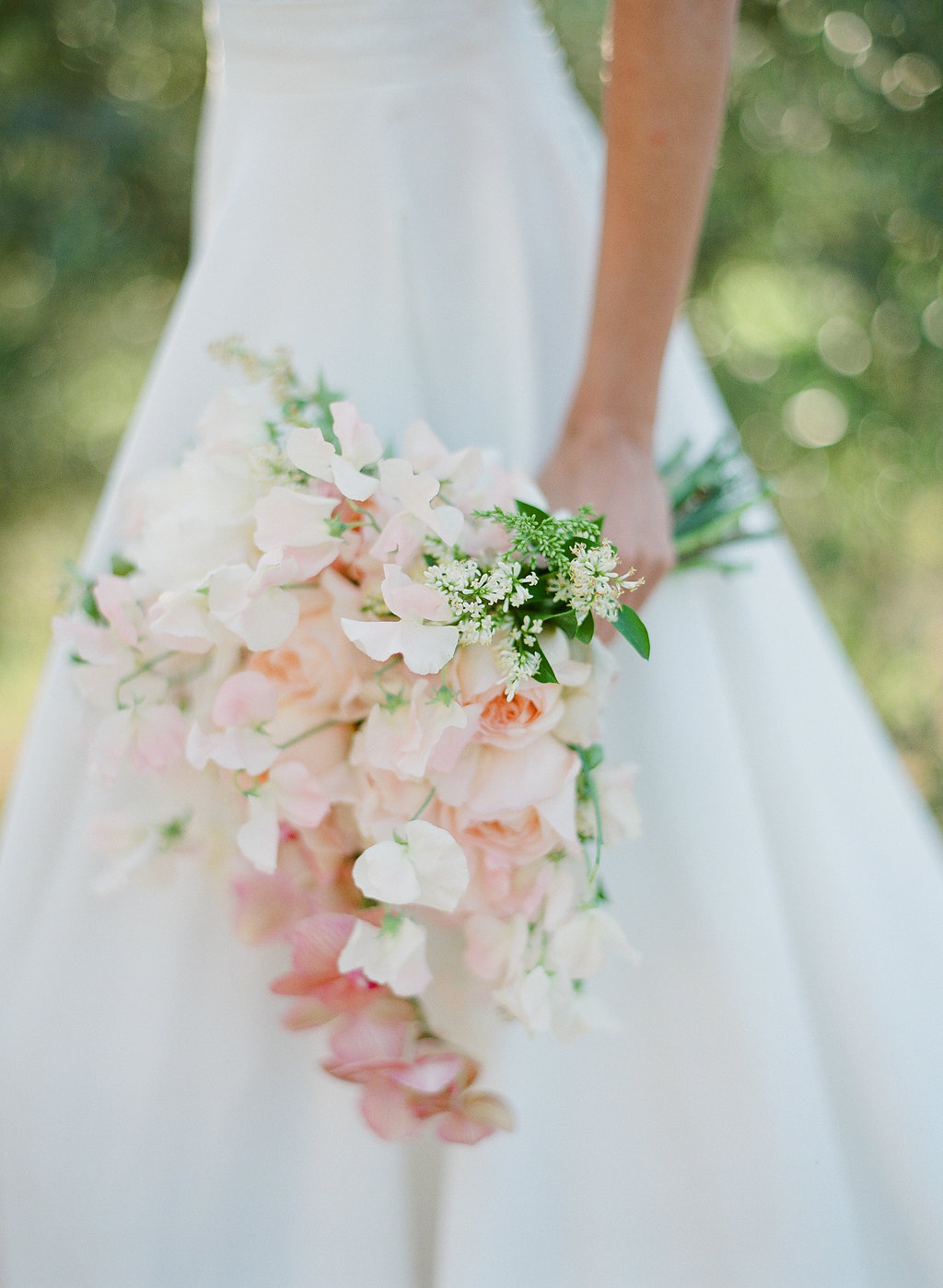 bride holding a beautiful orchid and rose bouquet
