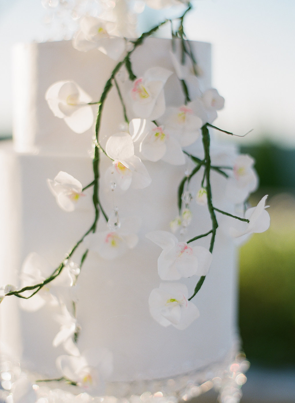 white wedding cake with cascading orchids