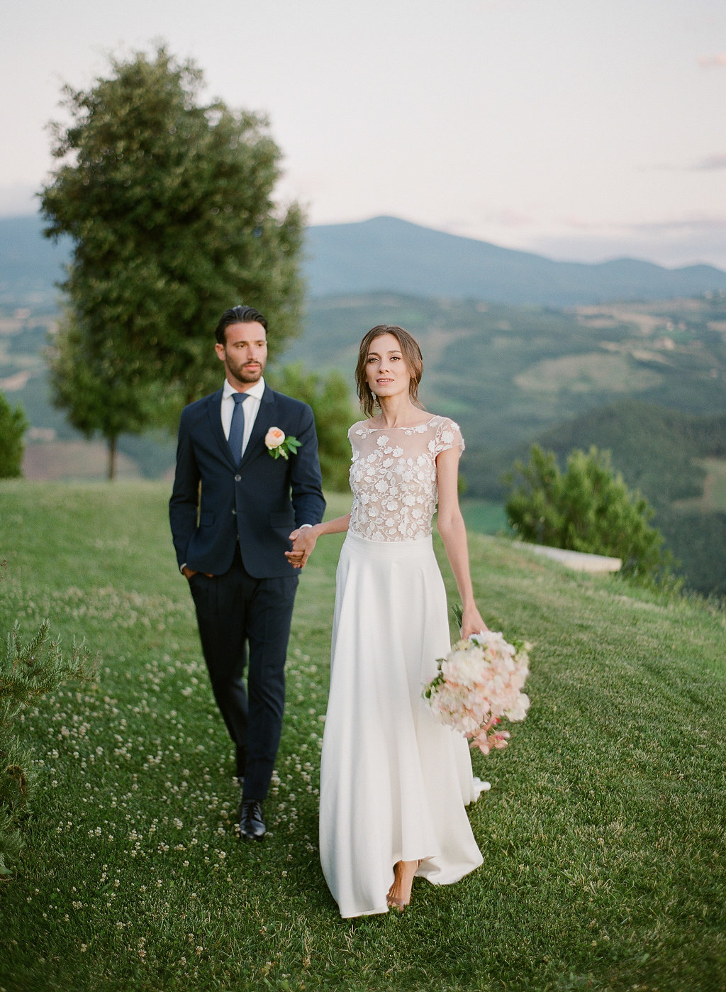 bride and groom walking along tuscan countryside