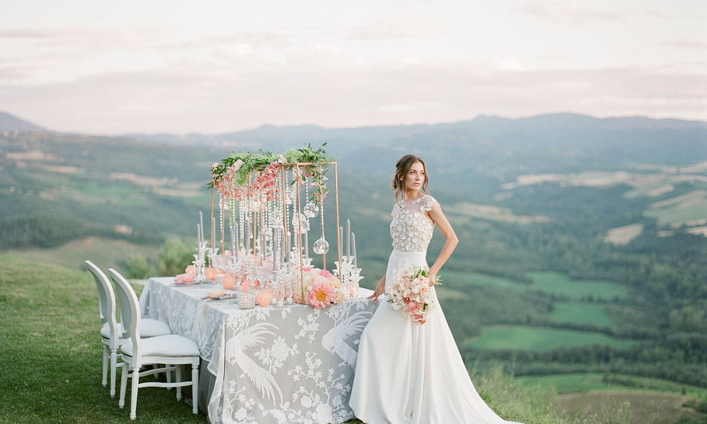 bride posing beside a coral and peach reception table in tuscany