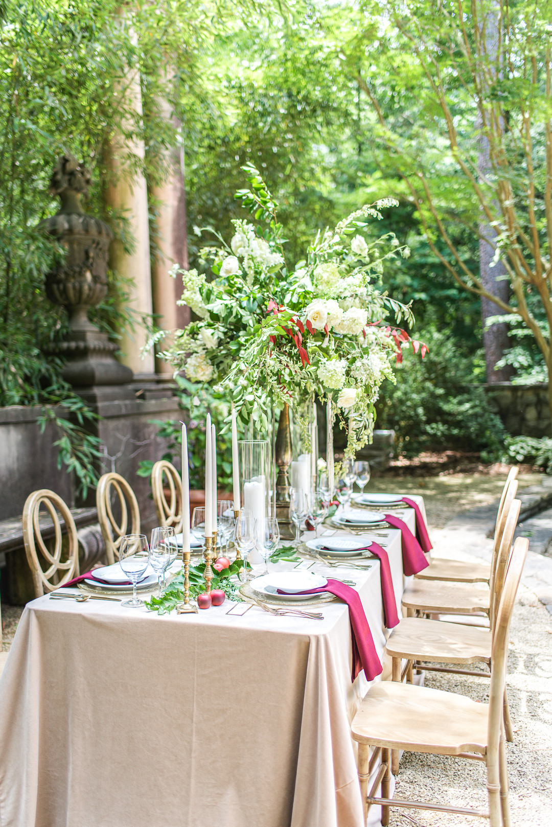beige table lines with red napkins and a large greenery centerpiece
