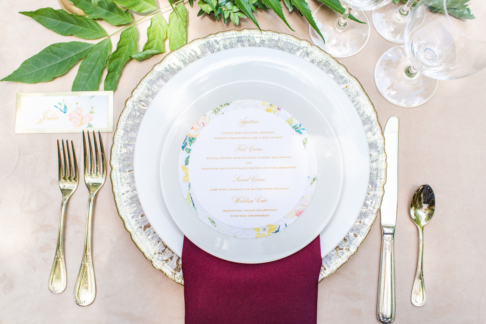 wedding place setting with a red napkin and printed circular dish menu