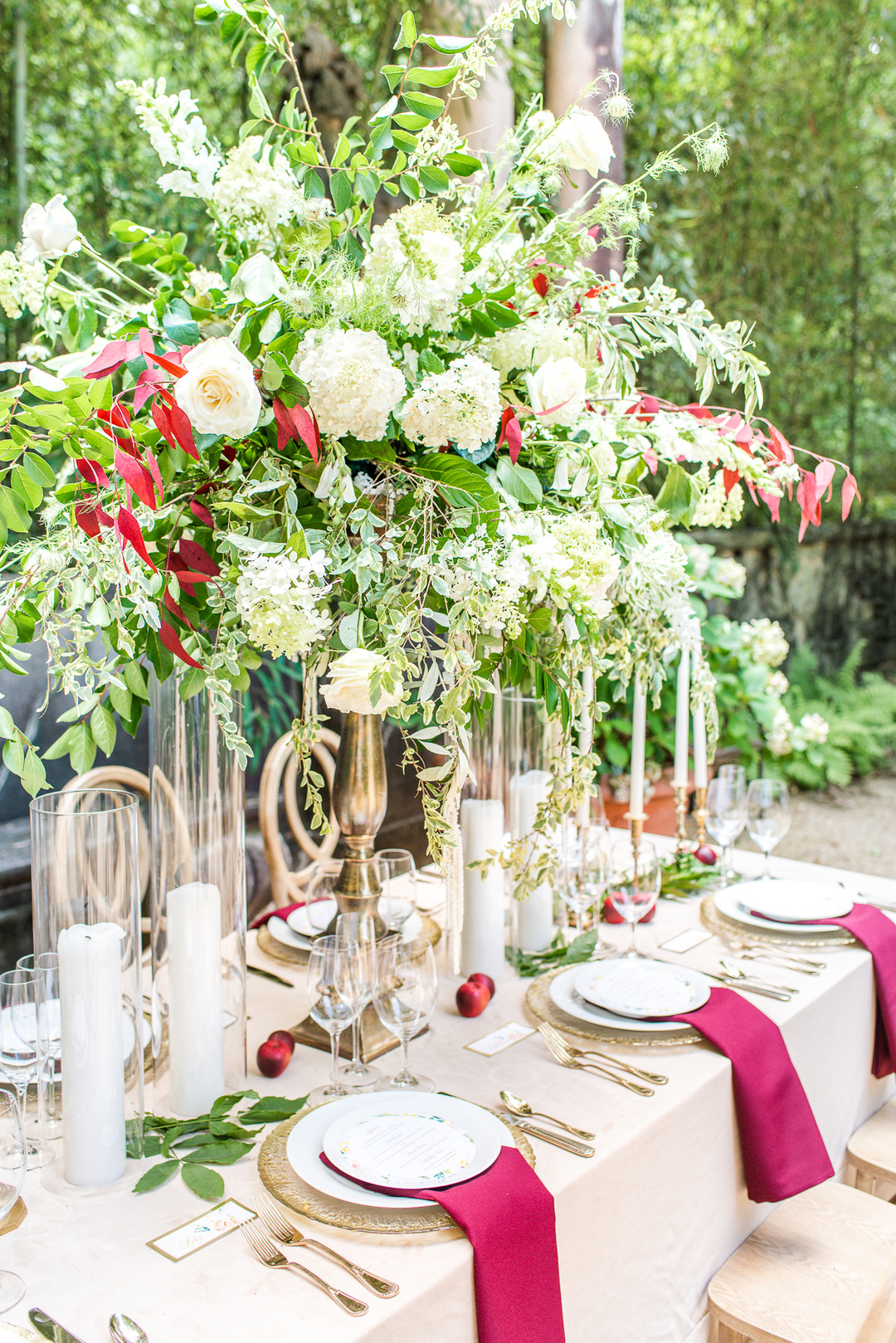 large, red, green, and white floral centerpieces on a table with red napkins and a beige tablecloth