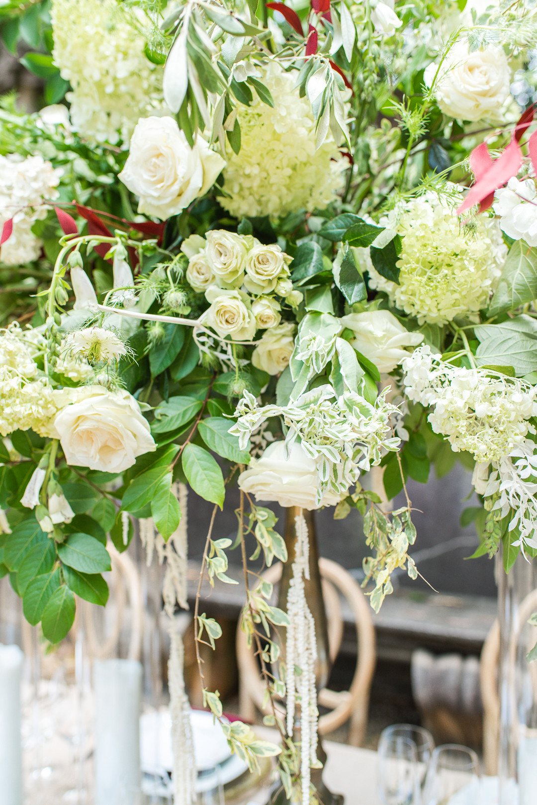 large centerpiece filled with greenery and ivory roses