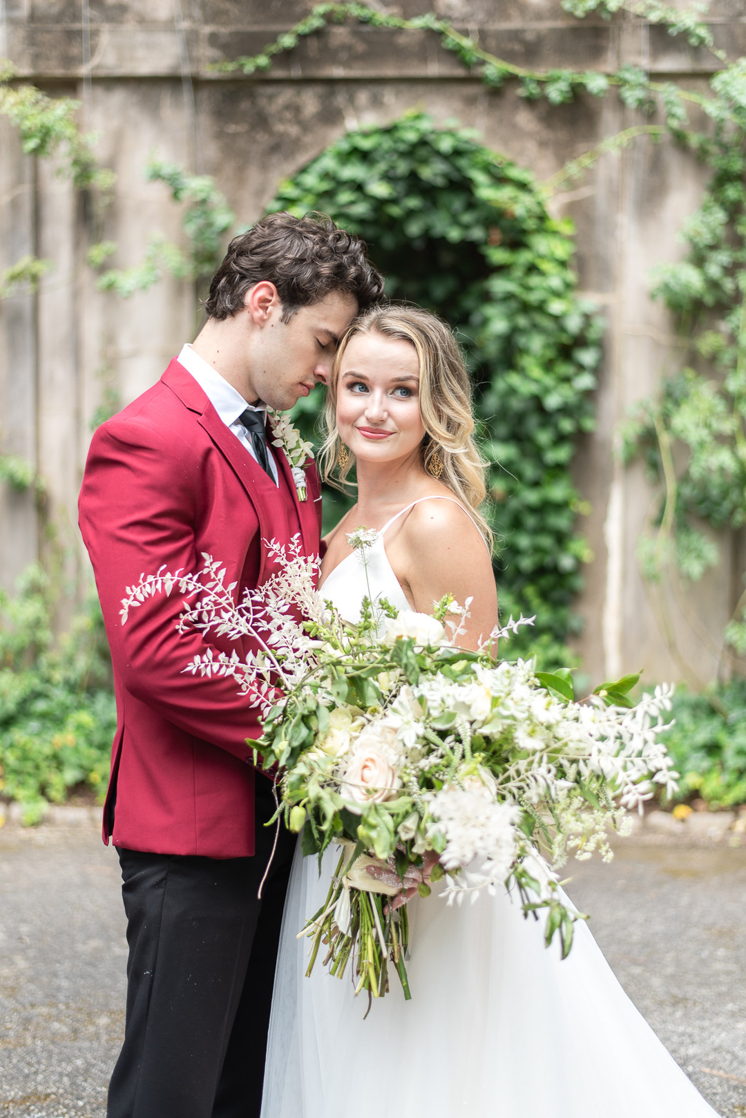 groom with red jacket and bride with large ivory and greenery bouquet