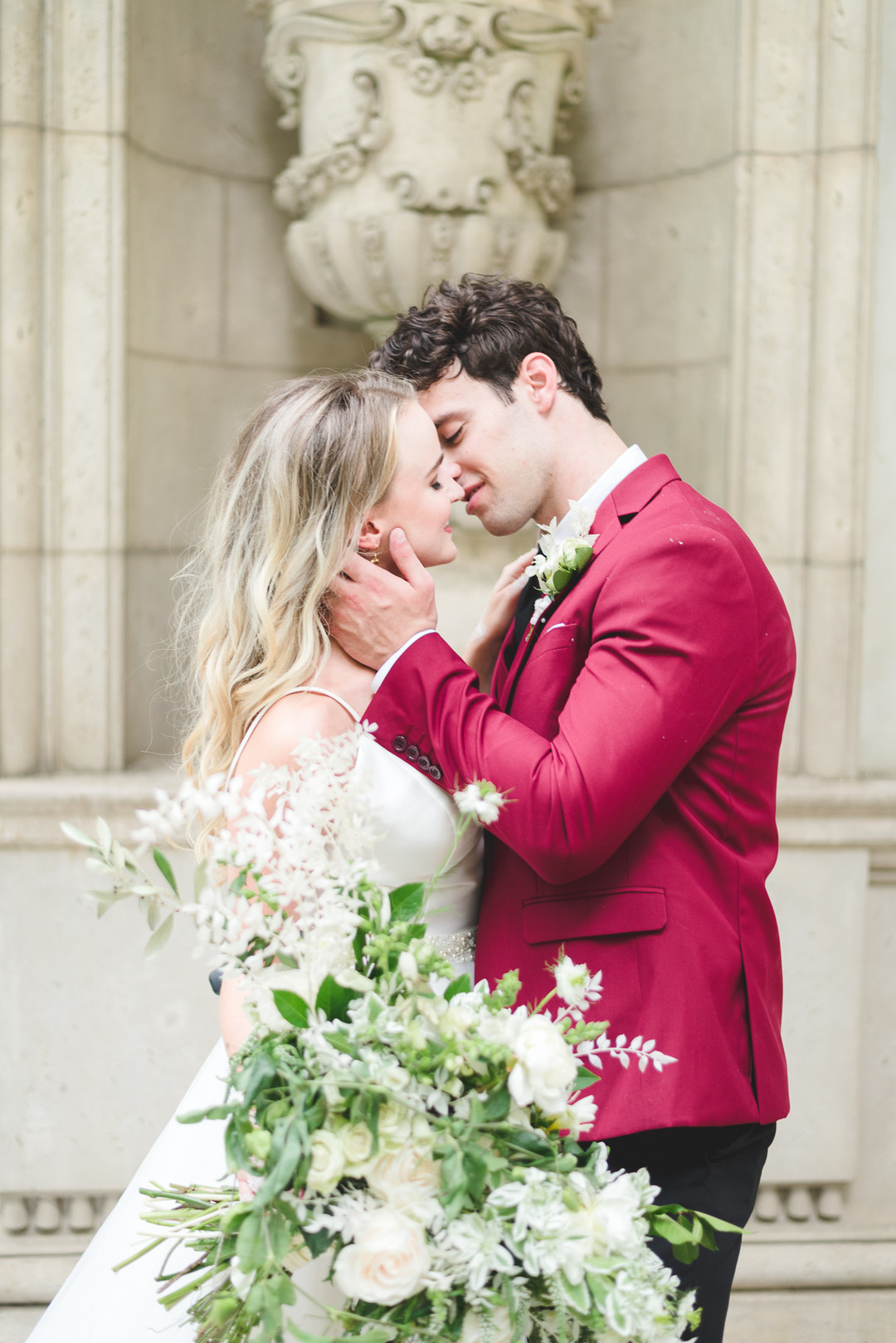 groom with a red jacket kissing his bride