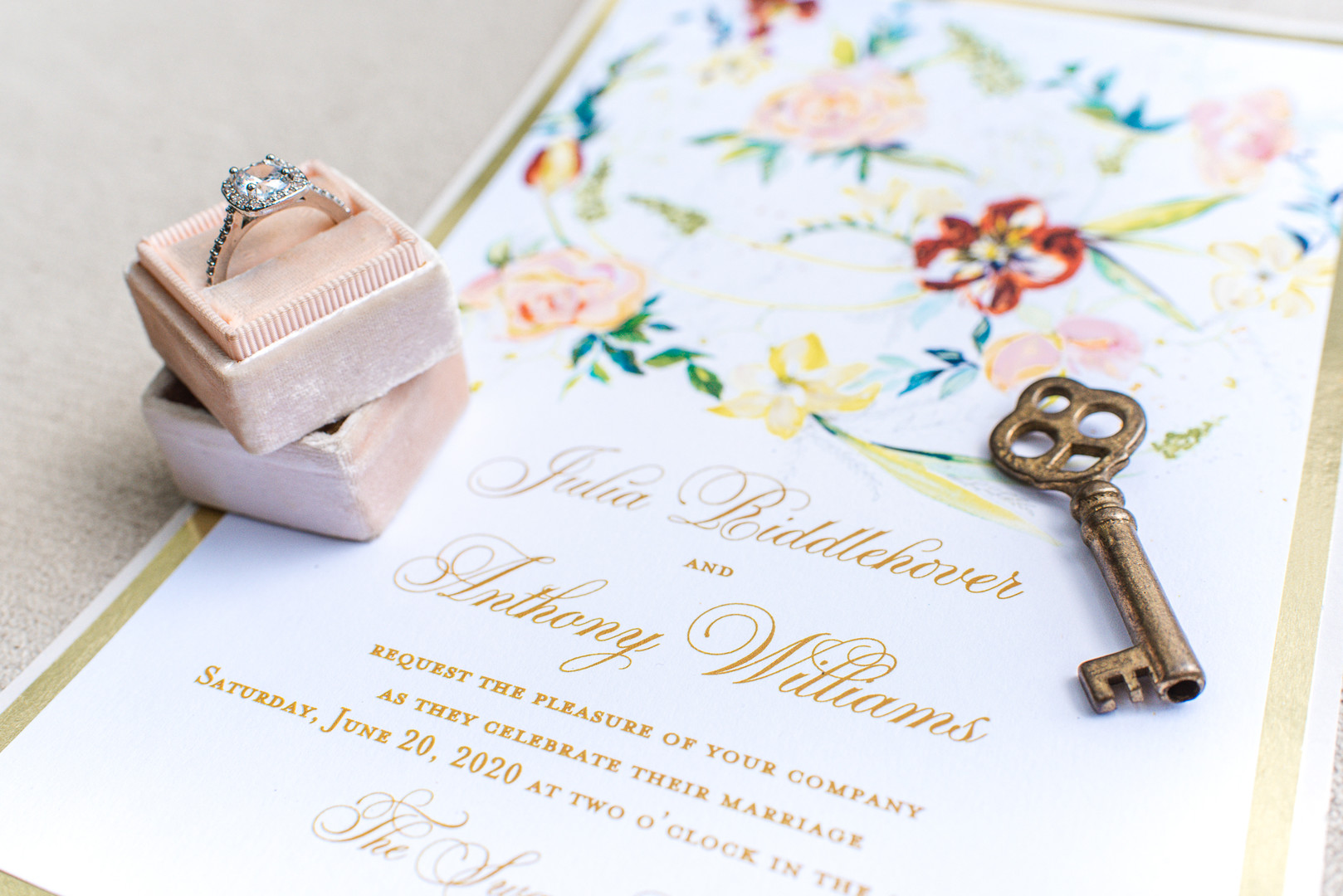 floral invitation suite flat lay with a vintage key and blush ring box