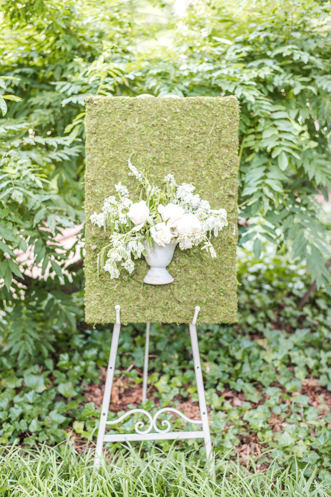 boxwood floral decor with fresh flowers on a welcome easel