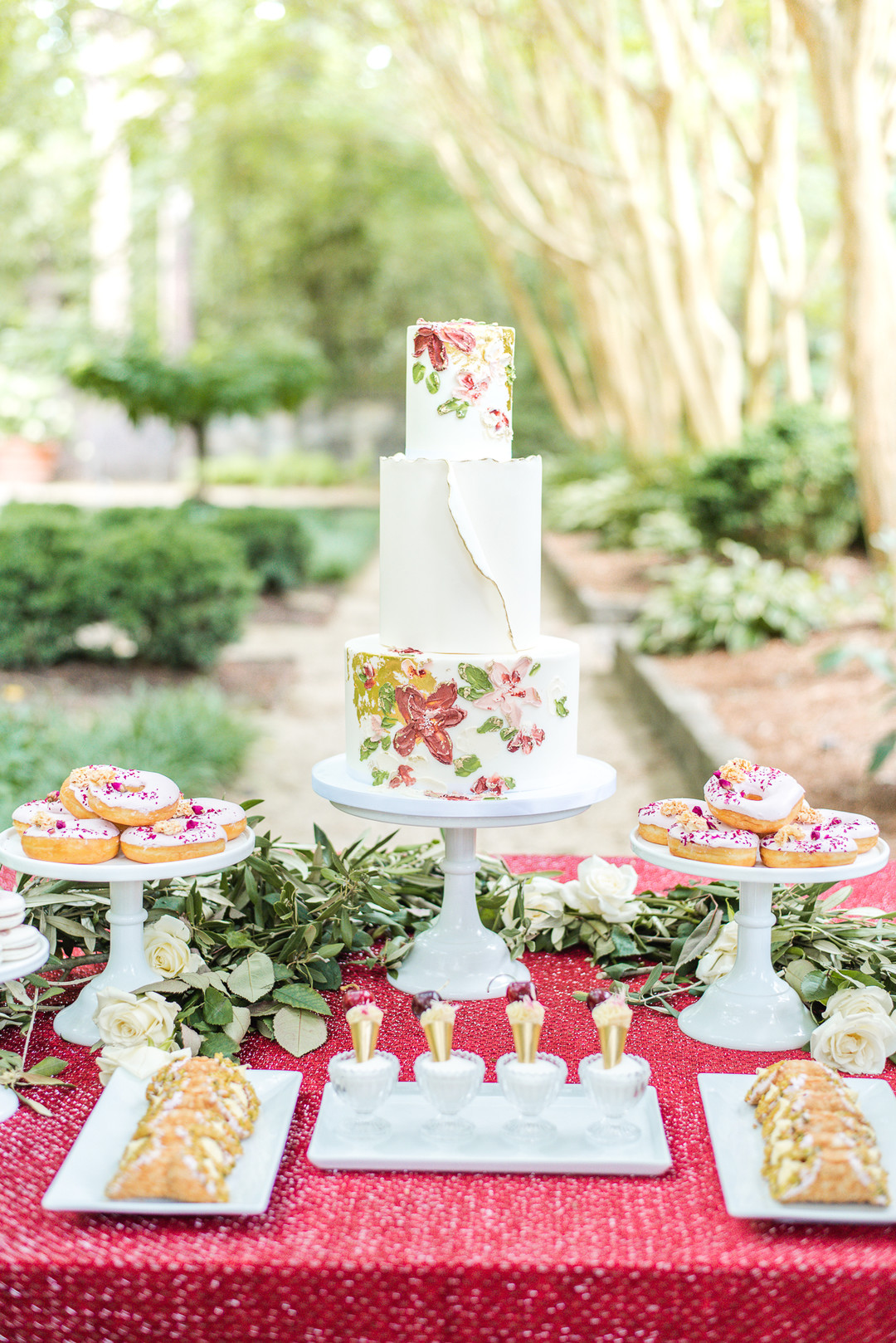 red and green floral cake surrounded by desserts on a red tablecloth