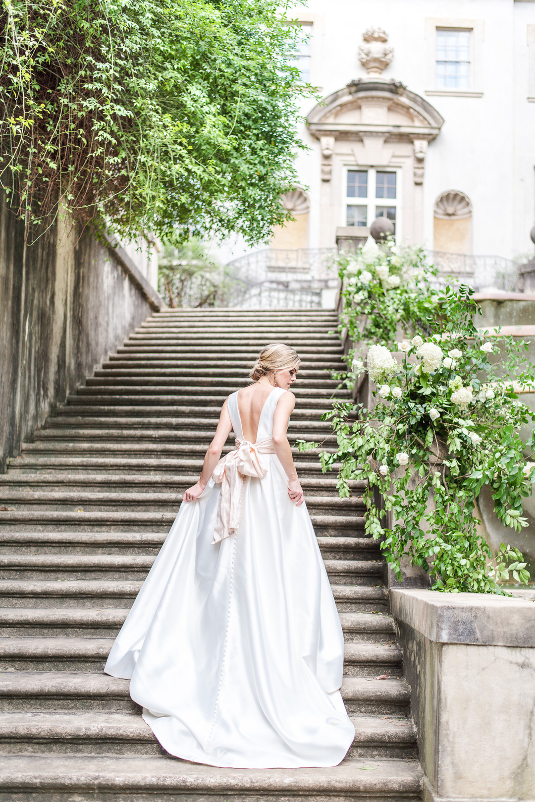 bride walking up the stairs of the swan house with a large blush bow on the back of her dress