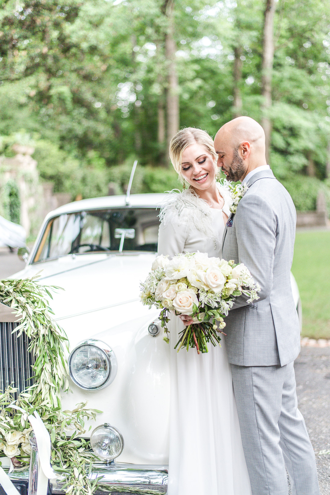 bride and groom posing in front of a white vintage car with a decorated front grill