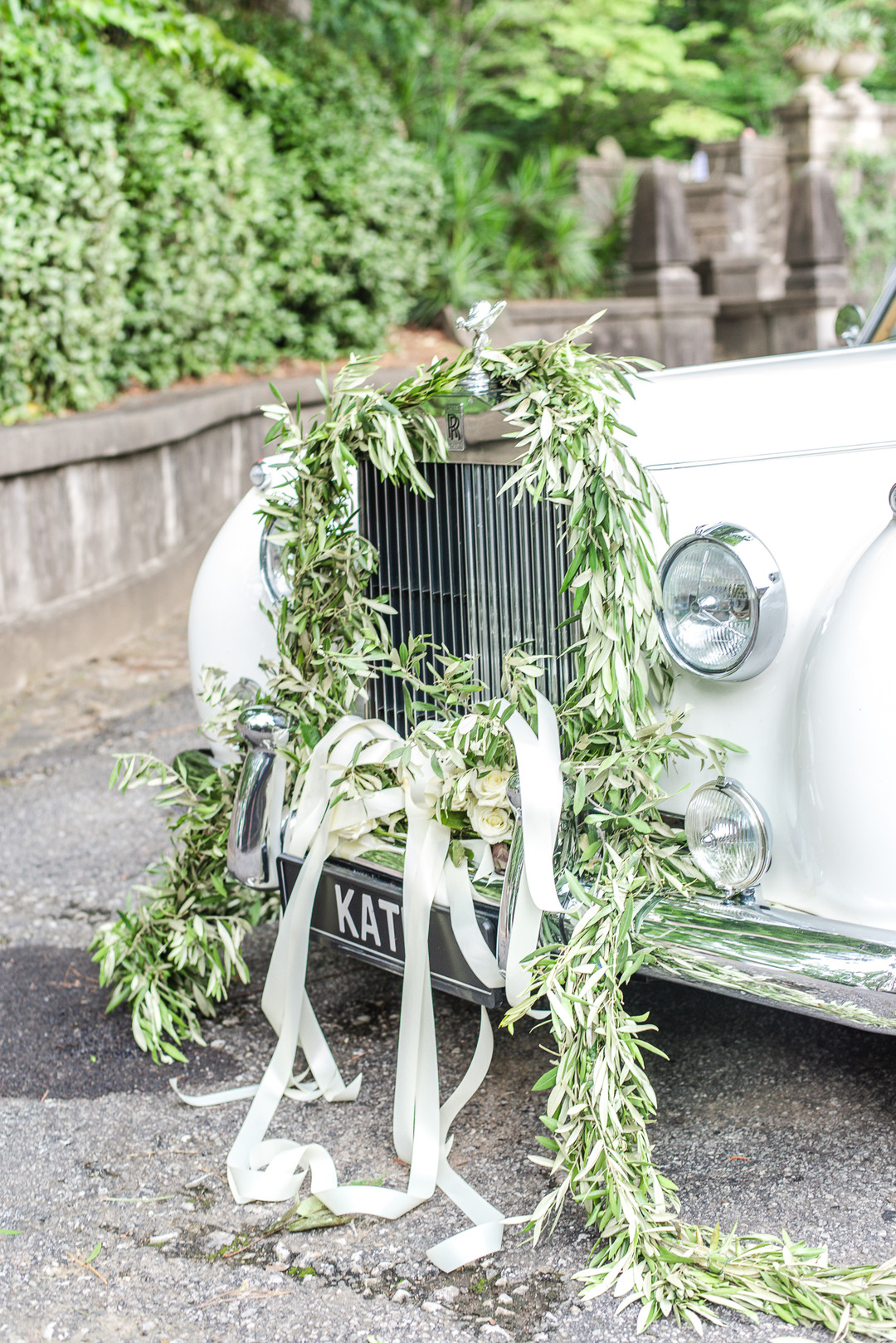 vintage car decorated with green vines and ribbon for wedding