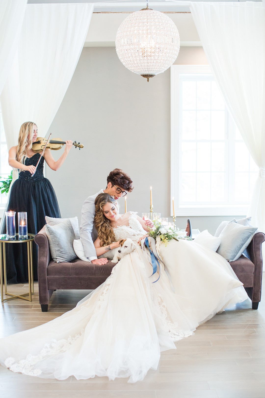 bride and groom sitting as violinist plays