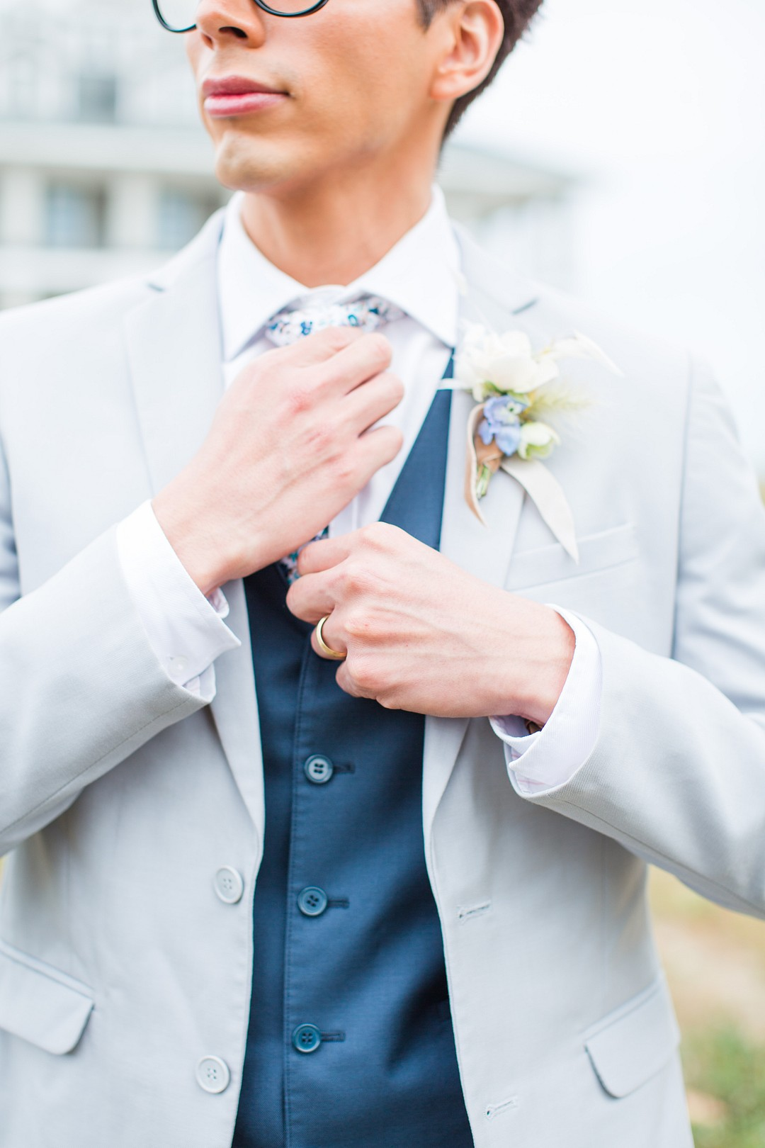 groom adjusting classic blue tie