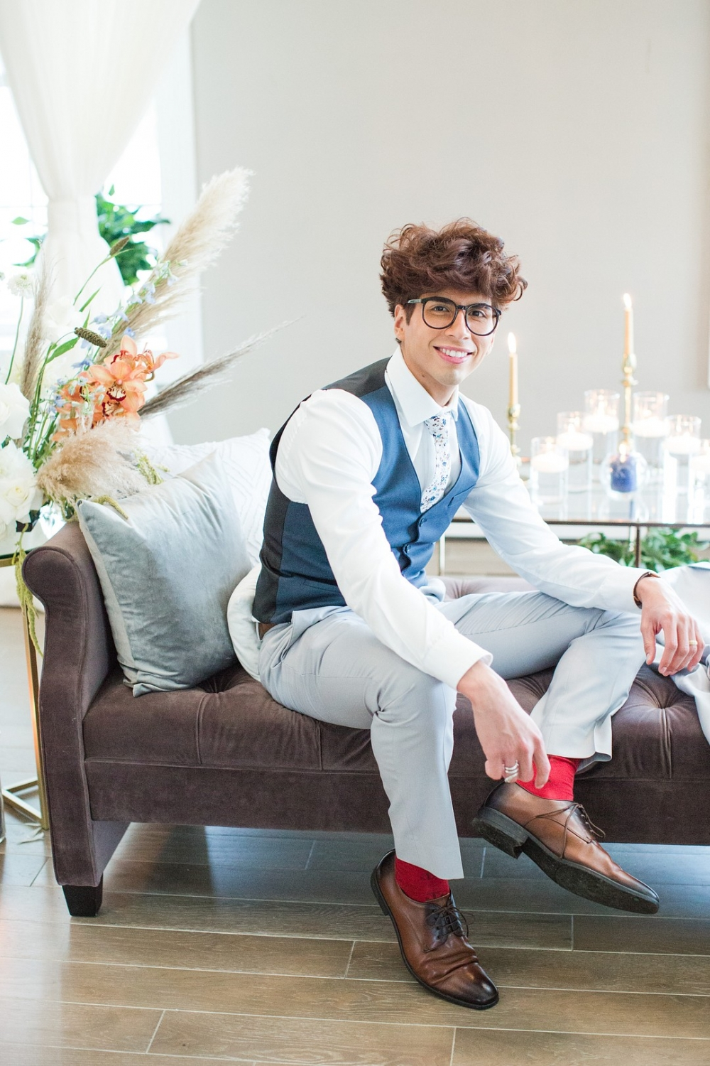 groom sitting on a chaise wearing a classic blue vest