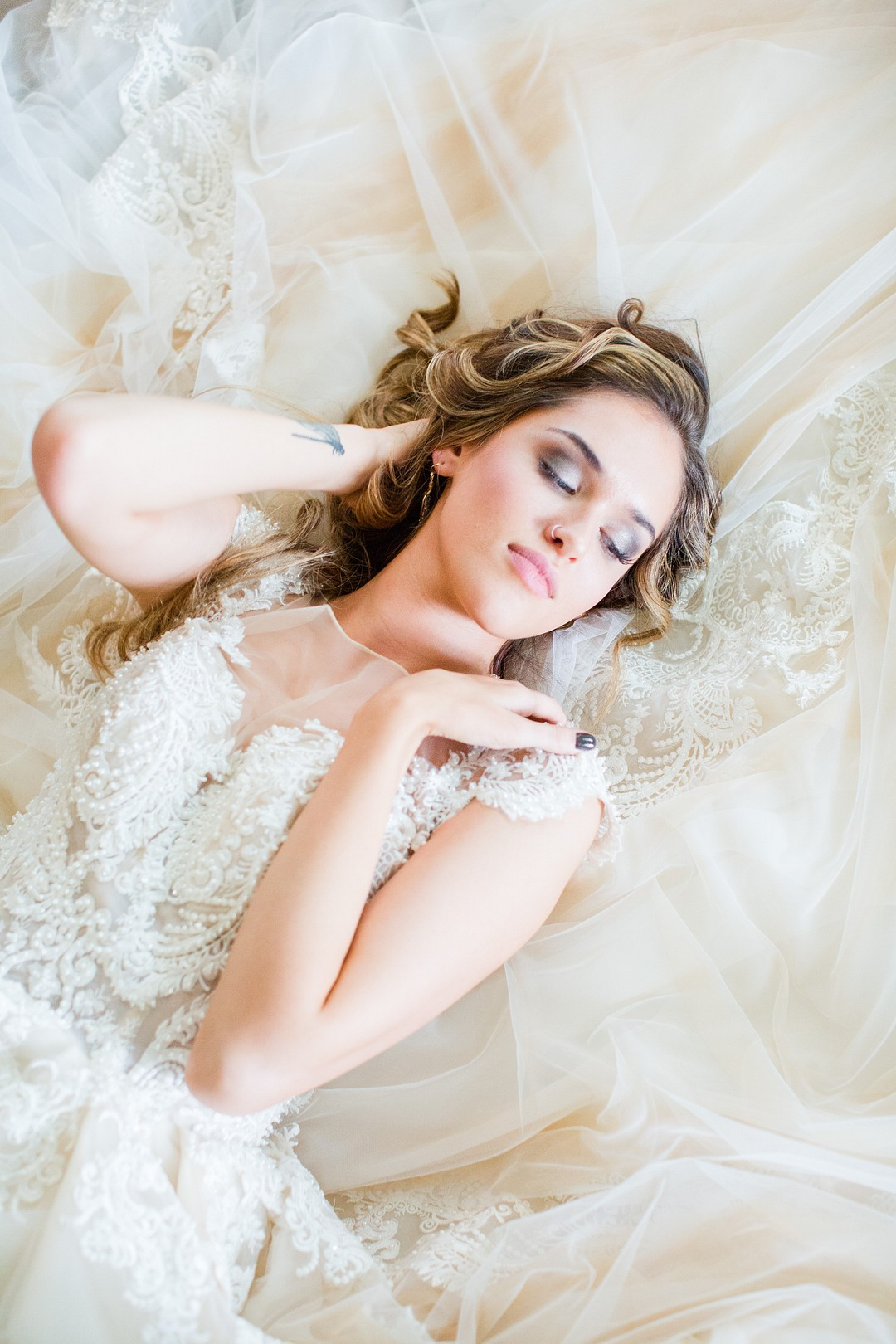 bride laying down on a long lace train