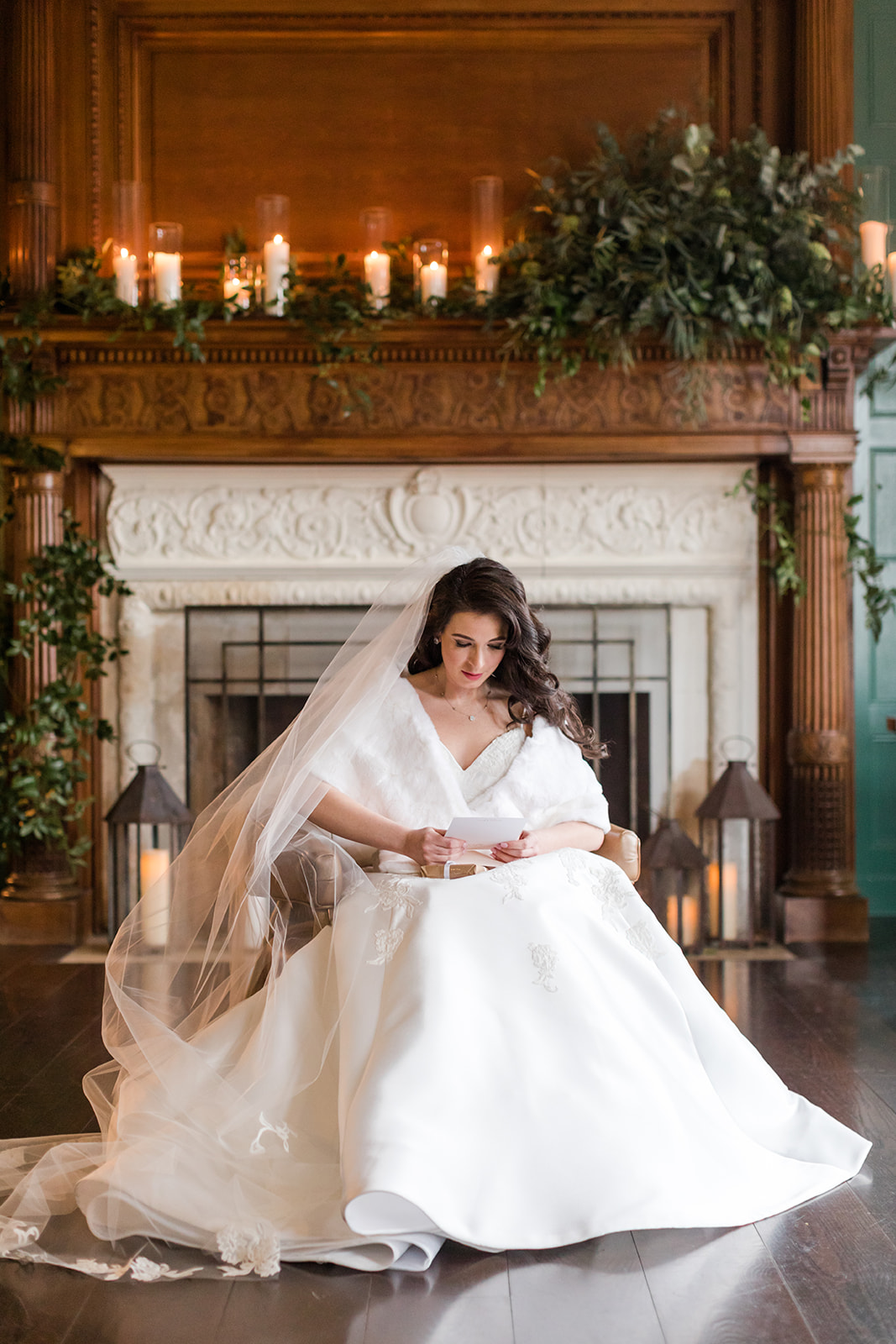 bride with fur overcoat sitting in fron of fireplace reading a letter from the groom