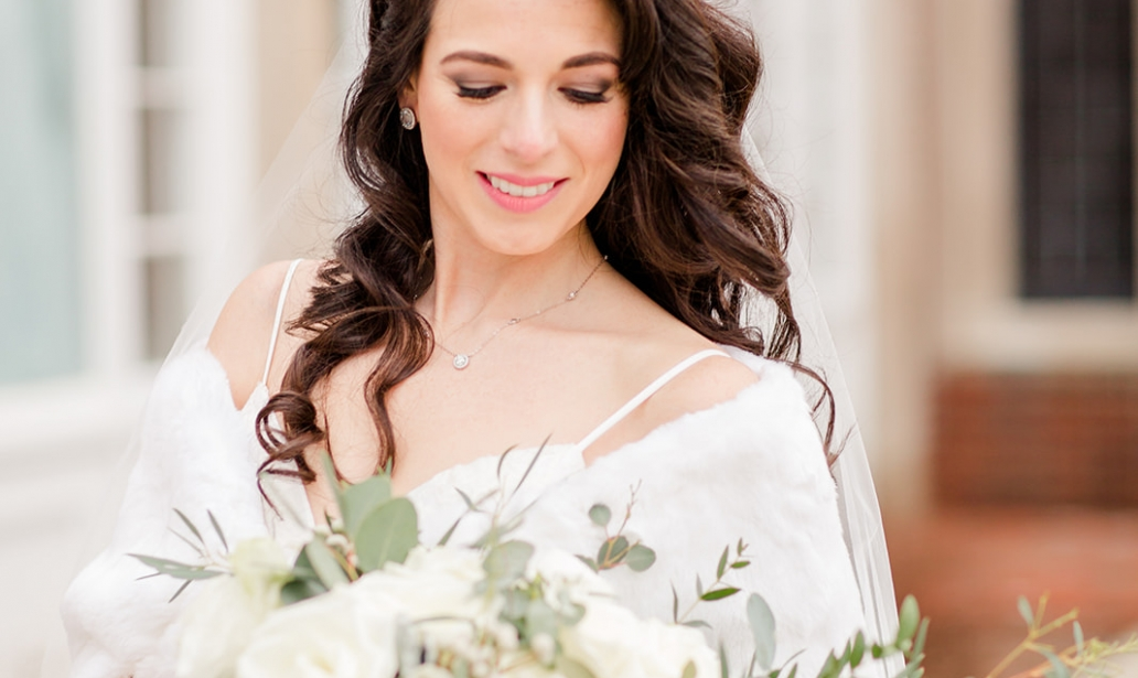 beautiful winter bride holding a white rose bouquet