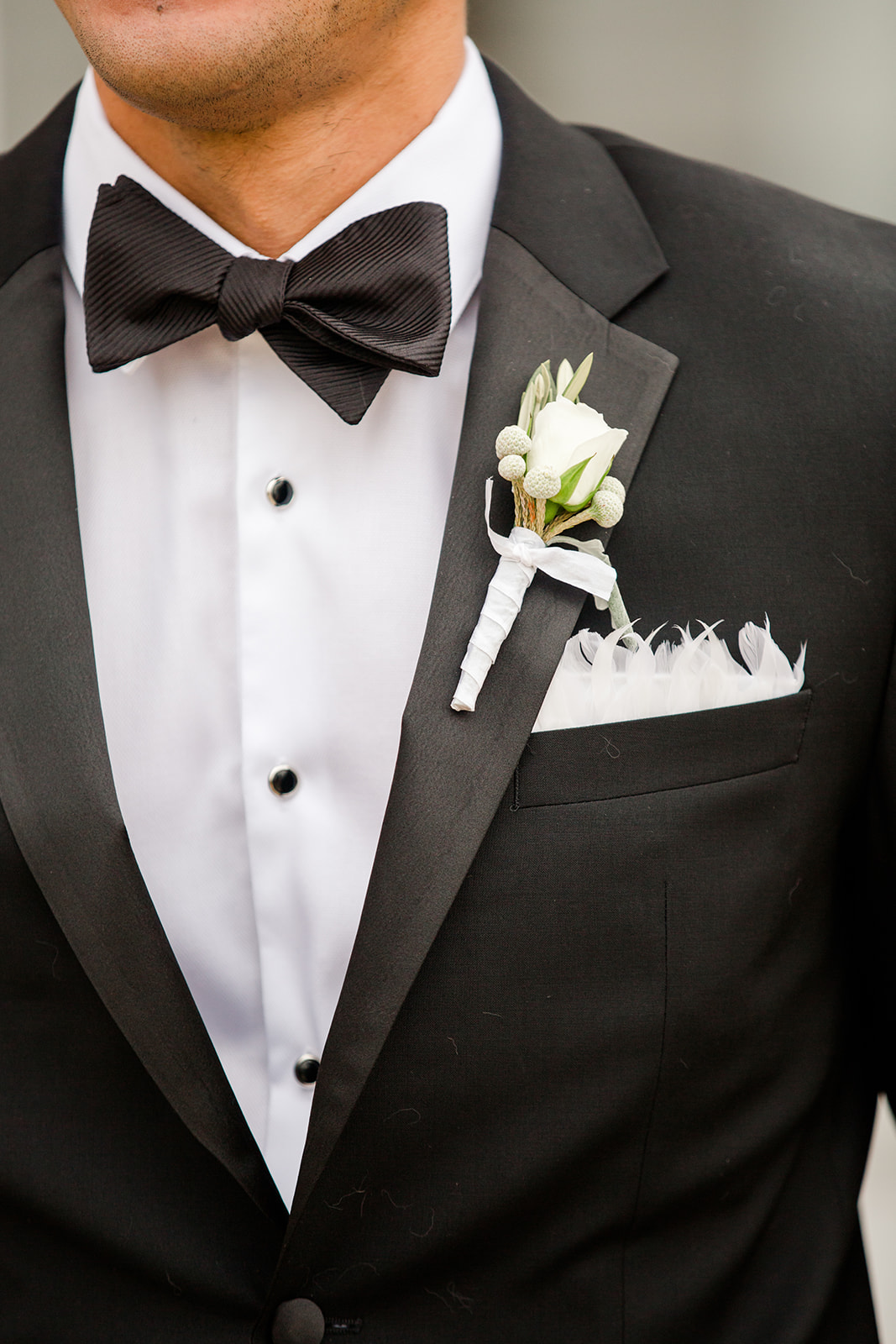 groom white rose boutonnier and white feathers in pocket