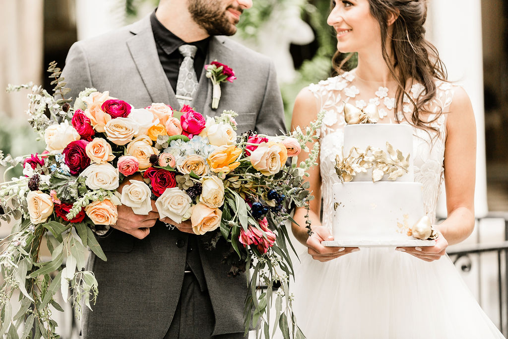 bride holding a cake and groom holding a bouquet